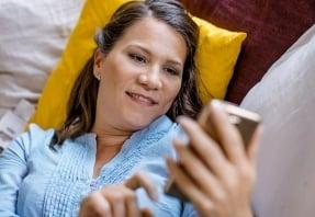 Nainen katsoo kännykästä jotakin